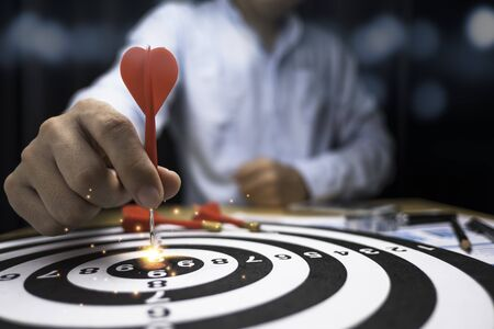 Businessman hand throw red arrow dart to target board. Business investment target concepts.