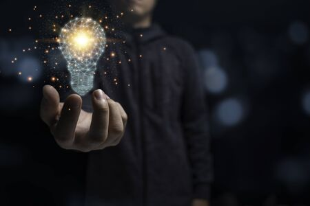 Businessman holding glowing virtual lightbulb with orange light . Creative new business idea concept. Zdjęcie Seryjne - 147683611
