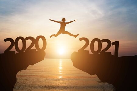 Man jump from year 2020 to 2021 with sunlight and sea. starting of new year concept.