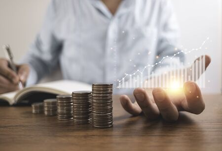 Businessman holding virtual graph and writing saving dividend or profit to notebook with coins stacking . Business investment and saving profit concept.