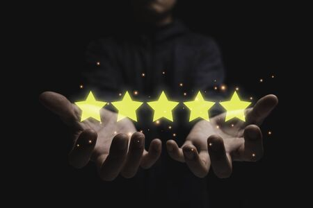 Businessman holding five golden star.Customer evaluation survey and satisfaction concept.