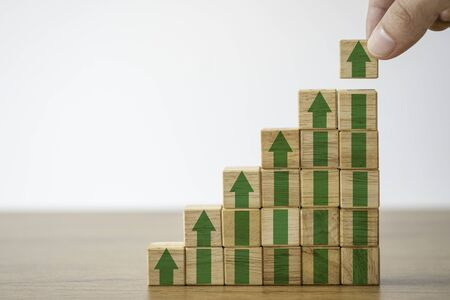 Hand putting wooden cubes block which print screen increase or up green arrow. It is symbol of economic investment profit growth.