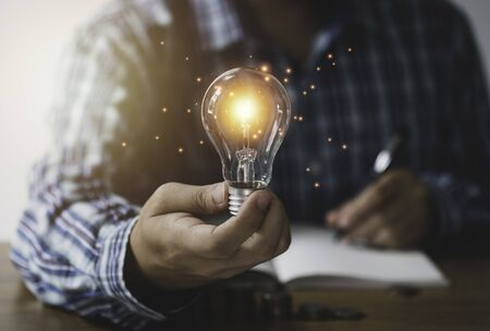 Businessman hand holding lightbulb with orange glowing and connection line. Creative thinking idea concept.