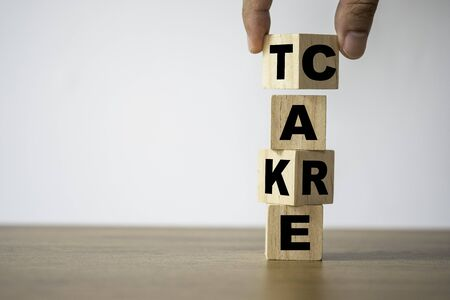 Hand Flipping of take care yourself wording which print screen on wooden cubes blocks on table.
