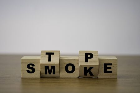 Flipping wooden cubes block which print screen stop smoking to good health condition.