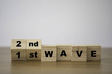 Flipping wooden cubes block for change 1st to 2nd wave to forecast COVID-19 coronavirus outbreak pandemic.