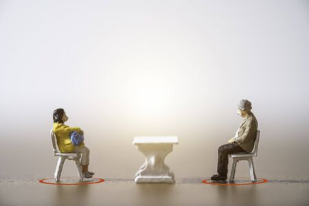 Old man and woman miniature people wearing face mask and sit down on chair by keep distance at public to prevent COVID-19 corona virus outbreak spread pandemic infection. Social distancing concept. Zdjęcie Seryjne