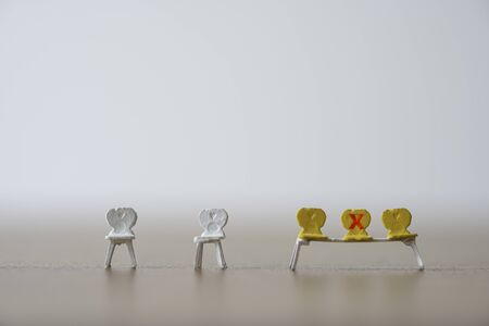 Yellow miniature chair which have Red Cross mark for prohibit sit down to keep distance at public and prevent COVID-19 corona virus outbreak spread pandemic infection. Social distancing concept.