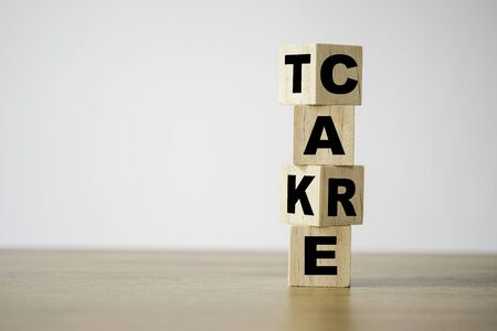 Flipping of take care yourself wording which print screen on wooden cubes blocks on table.