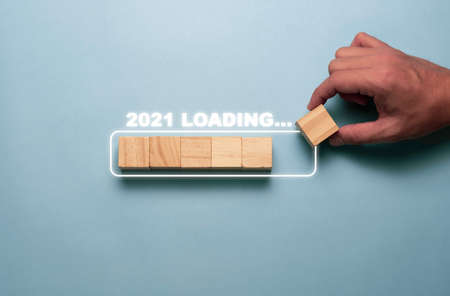 Hand putting wooden cubes block to  white block for count down and loading to 2021. Happy new year to start new project and business concept.