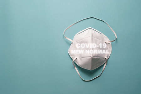White Surgical face mask for protection Corona virus or COVID 19 and dust PM 2.5 on green background . Healthcare and hygiene equipment concept.