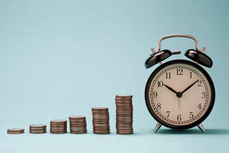Increase coins stack graph with alarm clock on blue background. Business investment time concept.
