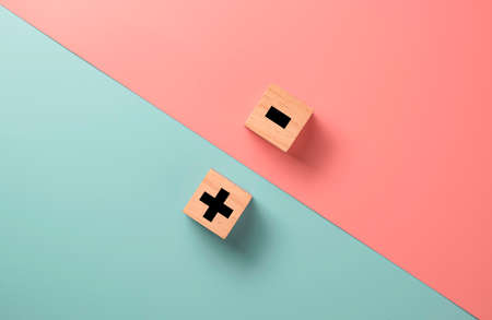 Black of plus and minus sign in opposite side of wooden cube on blue and pink