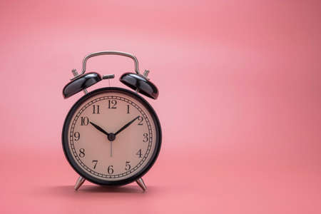 closeup of beautiful black alarm clock on pink background wit copy space.