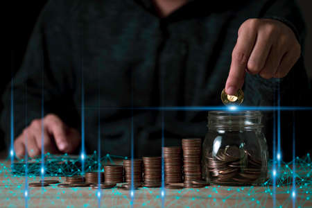 Hand putting coin to saving jar and coins stacking on table. Business investment growth and profit increase concept.