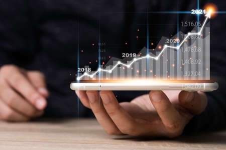Hand holding mobile phone with virtual arrow and investment graph. Business and profit growth concept.