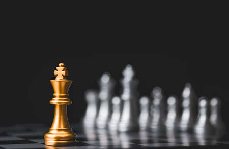Golden king chess stand alone among  silver chess enemy at opposite side. Strategy decision for marketing business with competitors company concept.