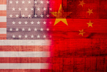 USA and China flag printed on wooden background .It is symbol of economic tariffs trade war and tax barrier between United States of America and China. Фото со стока
