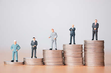 Business investment and planing concept , Businessman miniature figure standing on coins stacking.