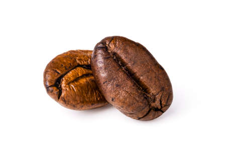 Two fresh roasted dark brown arabica coffee beans isolated on a white background with clipping path. 스톡 콘텐츠