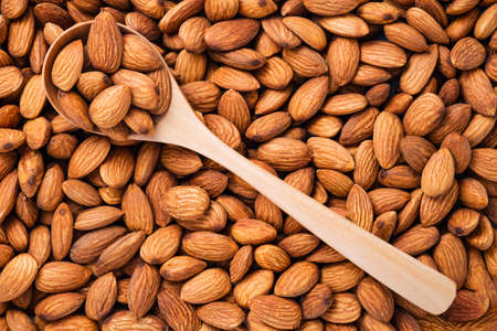Top view of fresh raw peeled almonds nut in spoon and background.