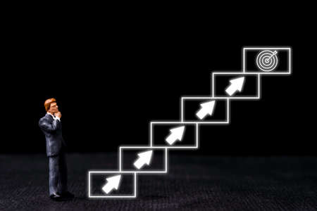 Achievement business target concept , businessman miniature standing and see virtual stair with step up arrow proceed until achieve objective target. Zdjęcie Seryjne