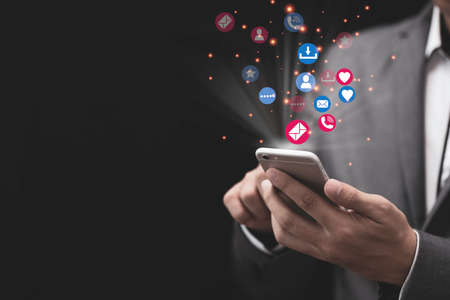 Social media and marketing concept, Businessman holding white smartphone and using colourful social media icons. Zdjęcie Seryjne