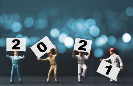 Merry Christmas & Happy new year holiday celebration concept , four Miniature figure worker staff holding and lift up number of 2021 year on blue bokeh background.