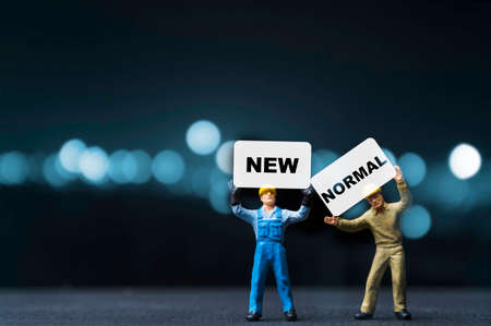 New normal concept , Miniature figure of staff worker hold and lift up white paper which screen new normal wording on blue bokeh background. Due to COVID-19 epidemic is accelerating the world change. Zdjęcie Seryjne