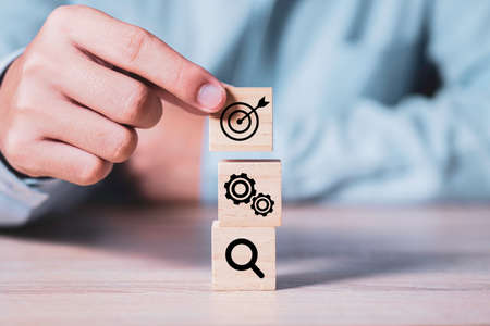 Achievement business target concept , businessman holding and stacking wooden cubes block which print screen target , mechanical gear , light bulb.
