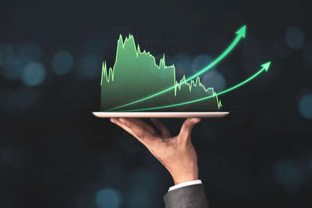 Businessman holding mobile & tablet which showing green technical stock investment graph with increase arrow. Value investor and analysis data concept.
