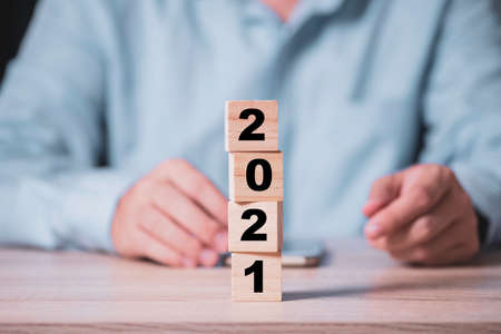 Businessman flipping wooden cubes block to change 2020 to 2021 year on wooden table. Happy new year and start new business concept. Zdjęcie Seryjne