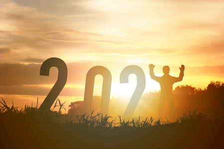 Happy new year 2021 silhouette concept  Human standing with number with beautiful orange sky for change to new year 2021.