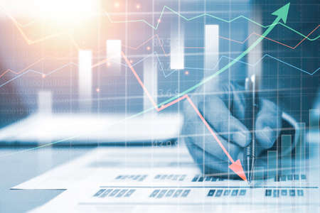 Double exposure of businessman writing on investment graph with virtual graph. Investment analysis and technical graph in stock market. Stock Photo