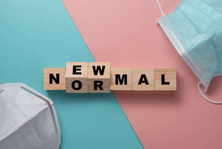 Flat lay of flipping wooden block cubes for new normal wording with surgical mask. The world is changing to balance it into new normal include business , economy , environment and health.
