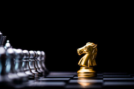 Golden horse chess encounters with silver chess enemy on chess board and black background. Market or business competitor concept.