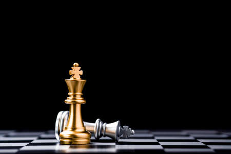 Stand of golden king chess and fallen silver king chess on chessboard. Winner of business competition and marketing strategy planing concept. 免版税图像