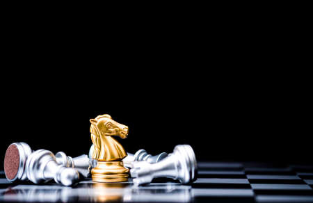Golden horse chess stand alone with fallen silver chess pieces. Winner of business competition and marketing strategy planing concept. 免版税图像