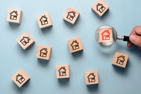 Hand holding magnifier glass to searching red house icon on wooden cube block among black house icon. Finding the best house and real estate for family concept. Stock Photo