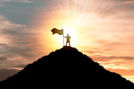 Business achievement objective  target and successful  concept , Silhouette Man standing and holding flag on top of mountain with cloud sky and sunlight. Zdjęcie Seryjne