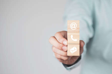 Businessman holding wooden cubes block which print screen Sign of e-mail , address and telephone for business marketing contact website page.