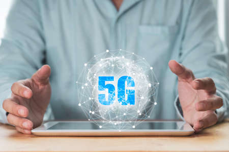 5G and internet of thing or IOT concept , Businessman protecting virtual 5G global networking on tablet.