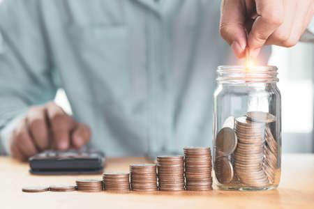 Save money and investment concept, Businessman putting coin to saving jar with coins stacked and using calculator,