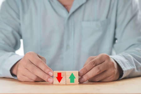 Business increasing or decreasing , Businessman holding green up arrow or red down arrow which print screen on wooden cube block. Zdjęcie Seryjne