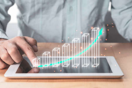 Stock market investment and business profit growth , Businessman pointing to tablet with virtual increasing graph and chart.