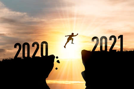 Welcome merry Christmas and happy new year in 2021,Silhouette Man jumping from 2020 cliff to 2021 cliff with cloud sky and sunlight. Zdjęcie Seryjne