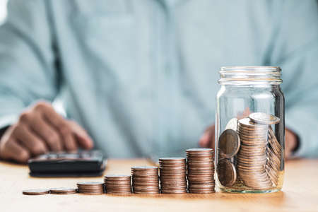 Save money and investment concept, Businessman putting coin to saving jar with coins stacked and using calculator.