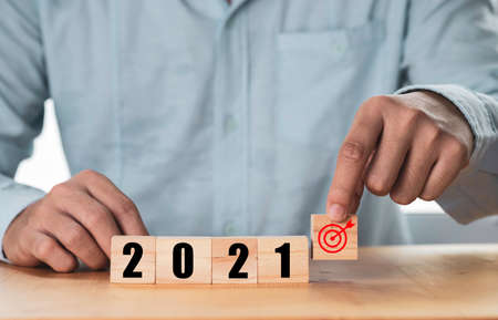 Businessman holding and putting target which print screen on wooden cube block with 2021 , Start new year and new target concept. Zdjęcie Seryjne
