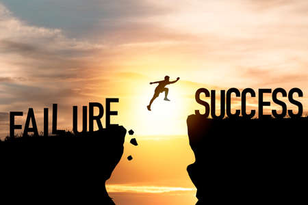 Mindset concept ,Silhouette man jumping from failure to success  wording on cliff with cloud sky and sunlight.