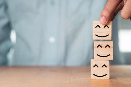 Select emotion or mood concept , Hand holding and stacking smile face  or happy face which print screen on wooden cube block.